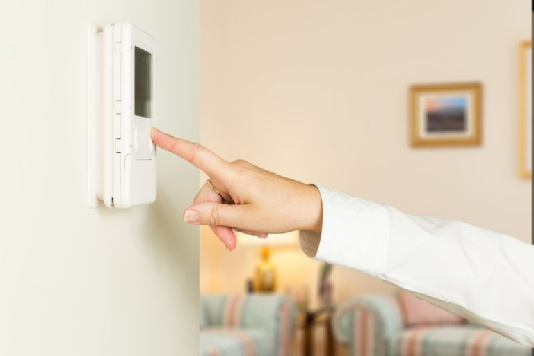 Woman adjusting thermostat of the room