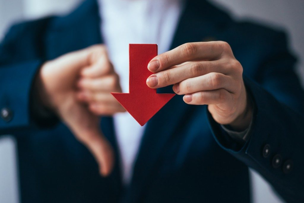 businessman holding a red arrow facing down